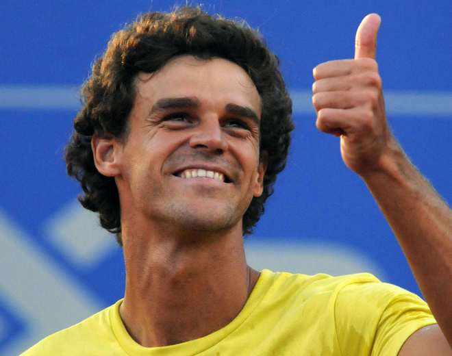 Brazilian tennis player Gustavo Kuerten gives the thumb up before playing his last competitive match in the Costa de Sauipe Open, in Brazil, and announcing his retirement from professional tennis on February 12, 2008. The 31-year-old three-times Roland Garros winner has been sidelined with hip injuries over the last three years and he has already said that he is planning to retire this summer after one final appearance in Paris. His French Open wins were in 1997, 2000 and 2001. He also won the Masters Series final in 2000, the year he was briefly ranked No. 1 in the world.  AFP PHOTO/MARCELO RUSCHEL (Photo credit should read MARCELO RUSCHEL/AFP/Getty Images)